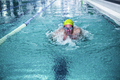 Fit man swimming with swimming hat in swimming pool