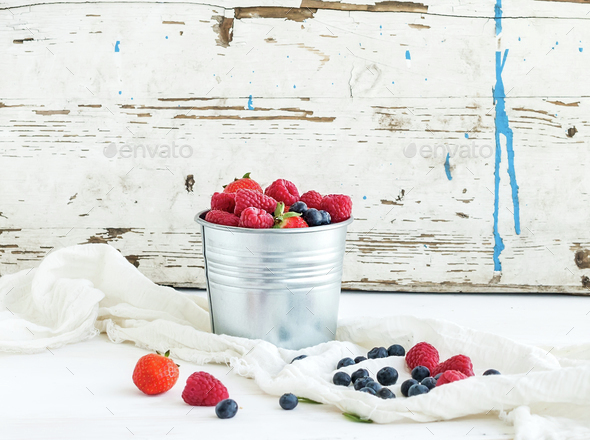 Metal bucket of strawberries, raspberries, blueberries and mint leaves, white wooden background - Stock Photo - Images