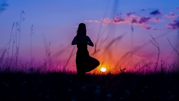 Silhouette Of A Young Girl Practicing Yoga Tree Pose At Sunset By
