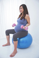 Beautiful asian pregnant woman doing exersice on a yoga ball, ho