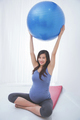 Beautiful asian pregnant woman doing exercise with a yoga ball,