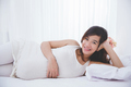 Beautiful pregnant woman smiling in to camera while lying on the