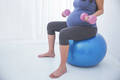 Pregnant woman doing exersice on a yoga ball, holding barbell in