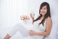 Beautiful pregnant asian woman holding a glass of milk, smiling