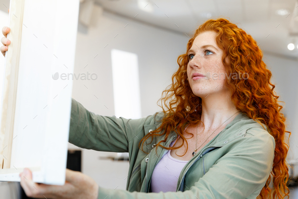 Young caucasian woman standing in art gallery front of  paintings - Stock Photo - Images