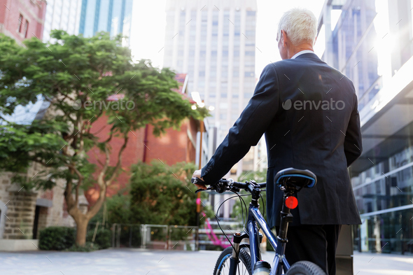 Successful businessman riding bicycle - Stock Photo - Images