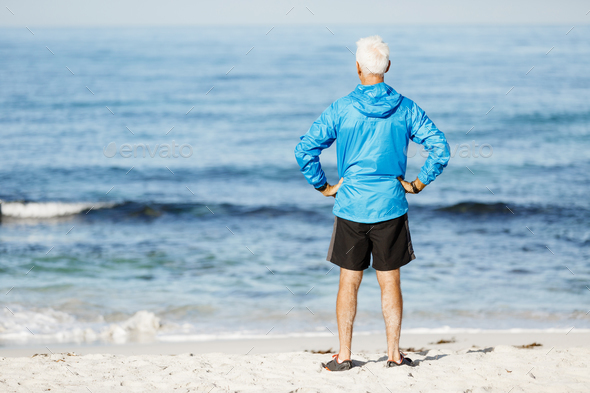 Handsome man looking thoughtful while standing alone on beach - Stock Photo - Images