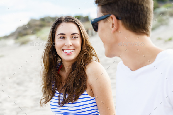 Romantic young couple sitting on the beach - Stock Photo - Images