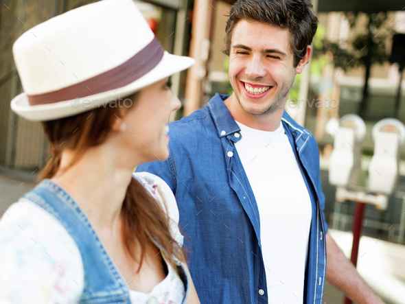 Happy young couple walking in city - Stock Photo - Images