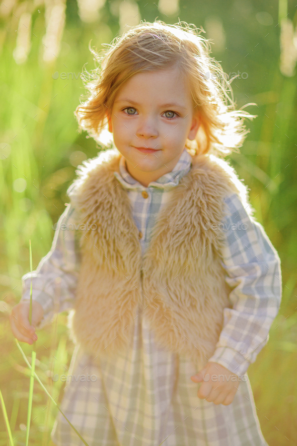 Cute curious girl at the green field in sunset - Stock Photo - Images