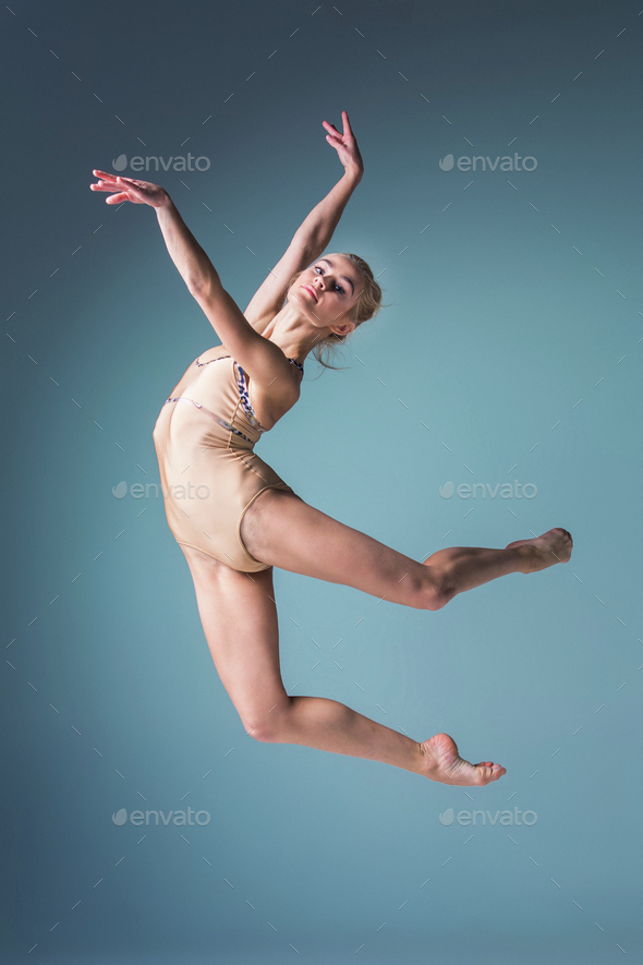 Young beautiful modern style dancer jumping on a studio background - Stock Photo - Images