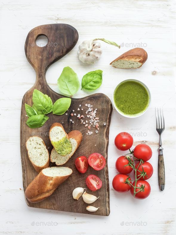 Pesto sauce, bread, cherry-tomatoes, fresh basil and garlic on rustic walnut chopping board - Stock Photo - Images