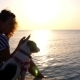 Young Woman With Dog Using Mobile Phone At Sunset - VideoHive Item for Sale