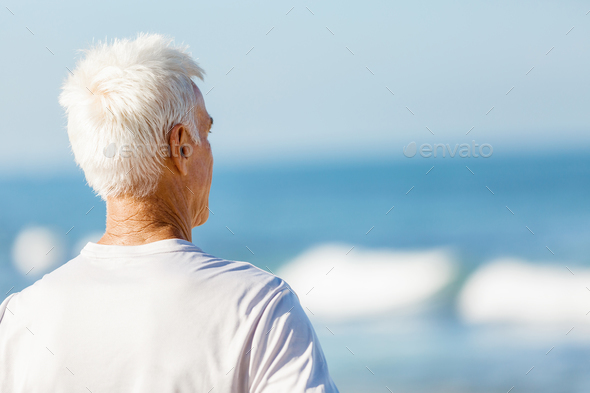 Man standing on beach in sports wear - Stock Photo - Images