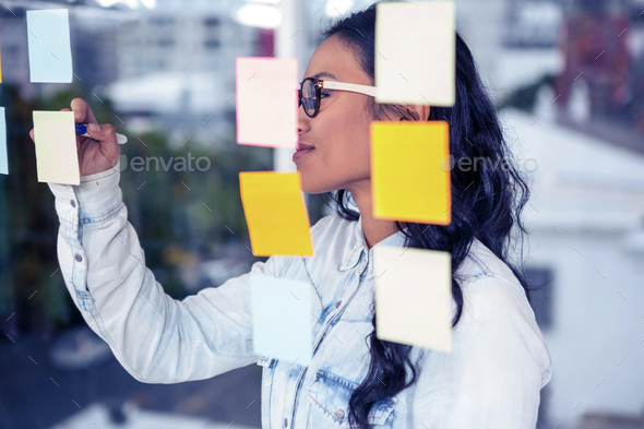 Asian woman writing on sticky notes on glass wall - Stock Photo - Images