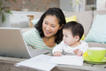 Happy mother with baby daughter using laptop in the living room - PhotoDune Item for Sale