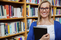 Happy female student holding a book in the library at the university - PhotoDune Item for Sale