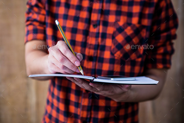 Hipster taking notes on notebooks on wooden background - Stock Photo - Images
