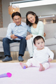 Happy parents looking at their baby daughter in the living room - PhotoDune Item for Sale
