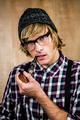 Serious blond hipster smoking a pipe staring at camera