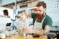 Barista pouring water in glass