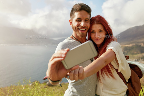 Young couple hiking taking selfie with smart phone - Stock Photo - Images