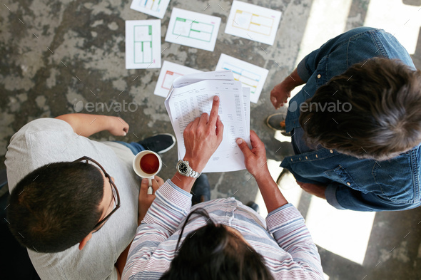 Business partners discussing financial data at meeting - Stock Photo - Images