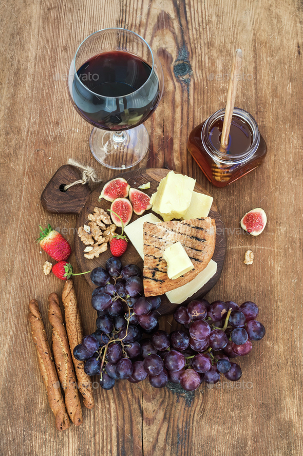 Glass of red wine, cheese board, grapes,fig, strawberries, honey and bread - Stock Photo - Images