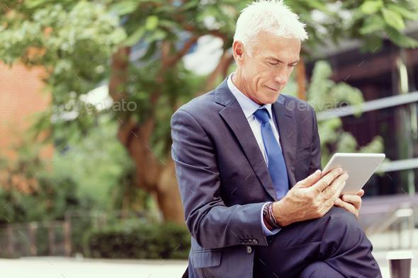 Senior businessman holding touchpad - Stock Photo - Images