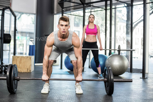 Fit couple lifting barbell at crossfit gym - Stock Photo - Images