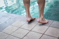 Close up of masculine feet at the edge of a pool