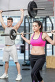 Fit couple lifting barbell at crossfit gym