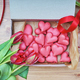 The box of heart-shaped macarons with flowers and ribbon on a wooden table. - PhotoDune Item for Sale