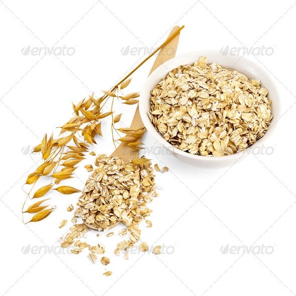 Rolled oats in a bowl and spoon - Stock Photo - Images