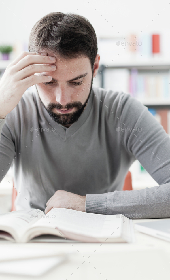 Man studying at the library - Stock Photo - Images