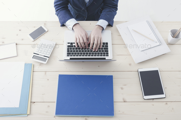 Office worker typing on a laptop - Stock Photo - Images
