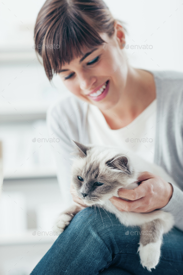 Smiling woman cuddling her cat - Stock Photo - Images