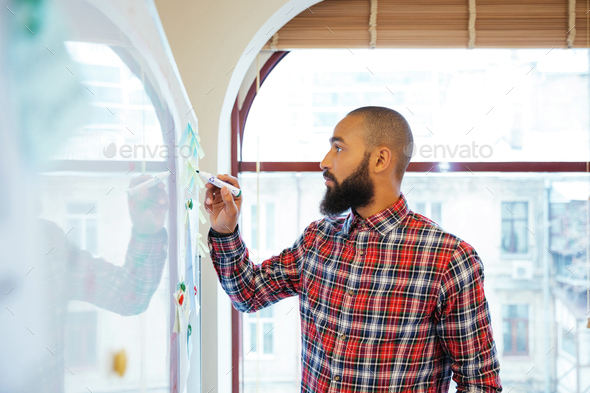 African man with beard standing and writing on whiteboard - Stock Photo - Images
