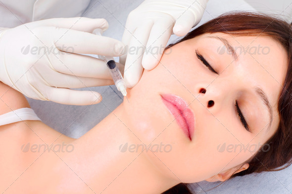 young caucasian woman receiving an injection of botox from a doctor - Stock Photo - Images