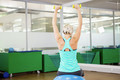 Fit woman lifting dumbbells and sitting on exercise ball in fitness studio