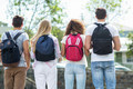 Rear view of hip friends with backpacks standing on the street