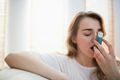 Woman using her inhaler on couch in the living room
