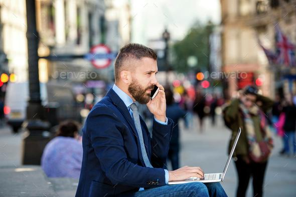 Manager with laptop and smart phone, sunny Piccadilly Circus, Lo - Stock Photo - Images
