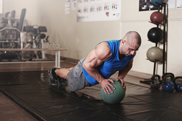 bodybuilder working out and doing push upsat the gym while - Stock Photo - Images