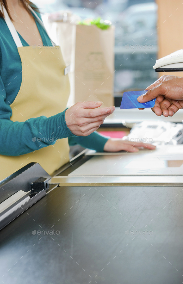 Customer handing a sales assistant a credit card - Stock Photo - Images