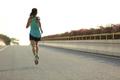 young fitness woman runner running on seaside bridge
