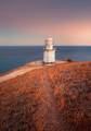 Beautiful white lighthouse on the ocean coastline at sunset. Lan
