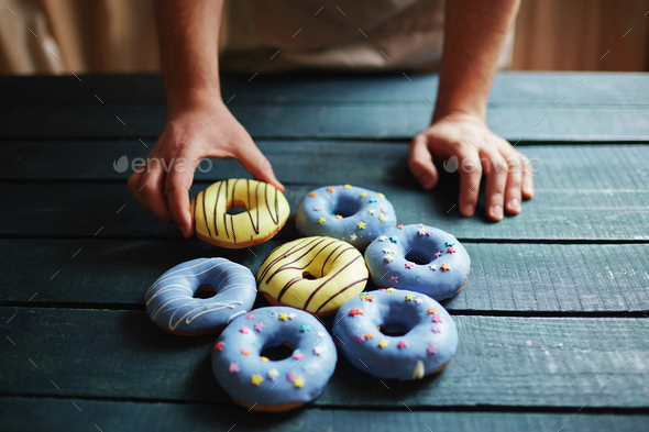 Putting donuts on table - Stock Photo - Images