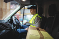 Delivery driver driving van with parcels on seat outside warehouse - PhotoDune Item for Sale