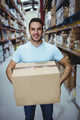 Smiling man holding big box in warehouse - PhotoDune Item for Sale